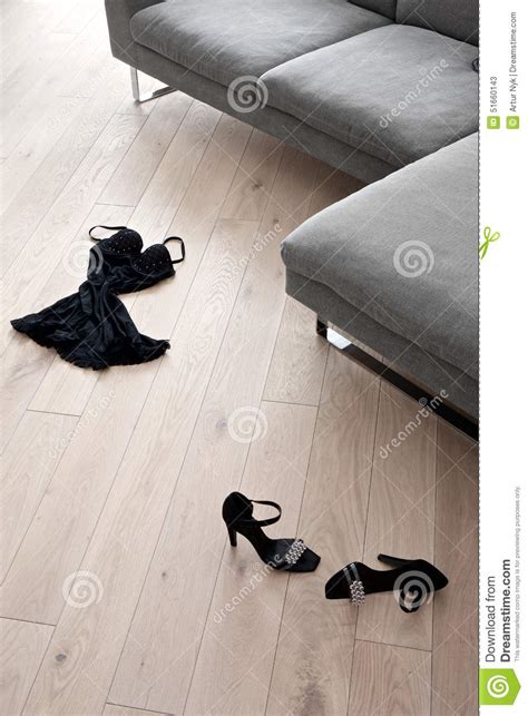 Women's Shoes And Clothes Lying In Front Of A Sofa Stock